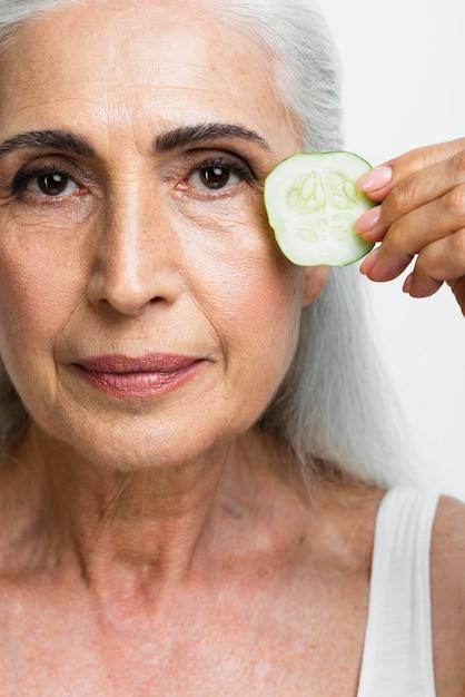 Mulher de close-up com fatia de pepino Foto gratuita