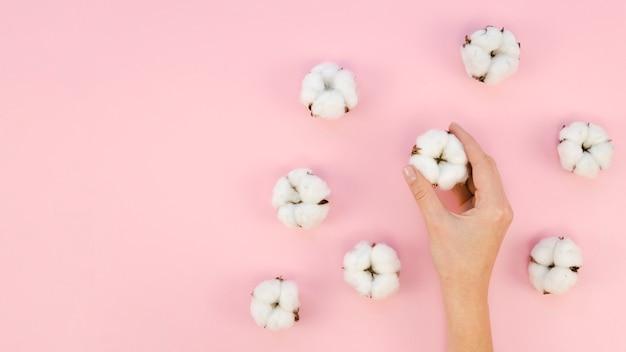 Mulher de close-up com flores de algodão Foto gratuita