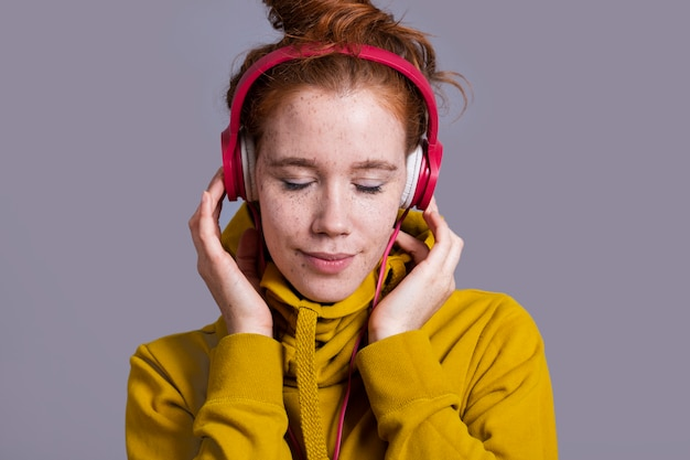 Mulher de close-up com fones de ouvido vermelhos e capuz amarelo Foto gratuita