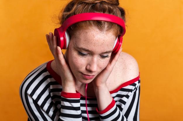Mulher de close-up com sardas e fones de ouvido vermelhos Foto gratuita