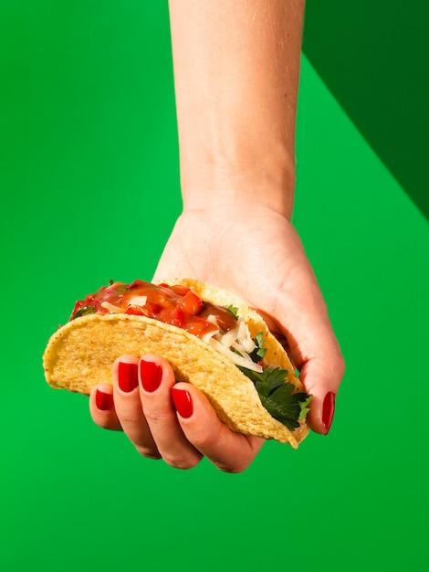 Mulher de close-up com taco e fundo verde Foto gratuita
