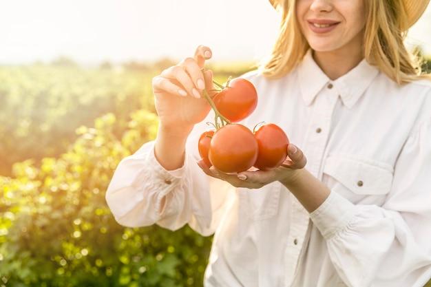 Mulher de close-up com tomates Foto gratuita