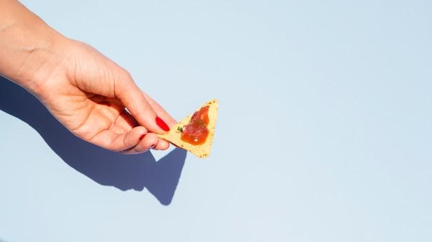 Mulher de close-up com tortilla chips e fundo azul Foto gratuita