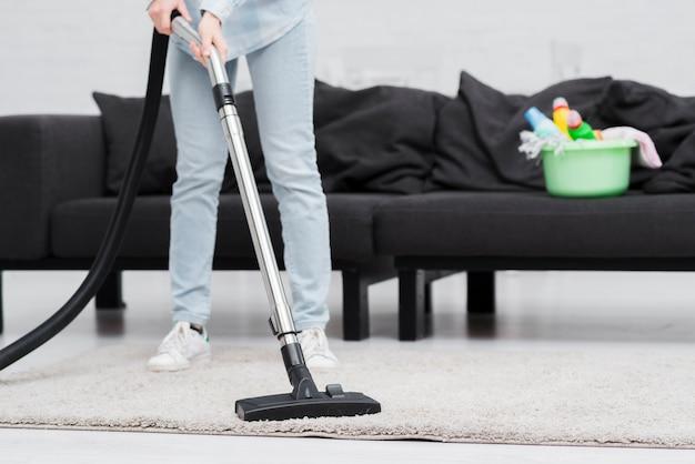 Mulher de close-up de limpeza com aspirador Foto gratuita