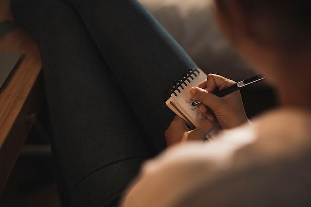 Mulher de close-up, escrevendo em um caderno Foto gratuita