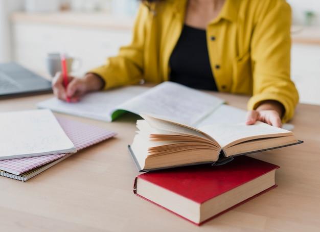 Mulher de close-up, escrevendo no caderno Foto gratuita