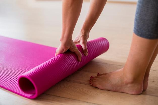 Mulher de close-up no sportswear, definindo o tapete de ioga Foto Premium