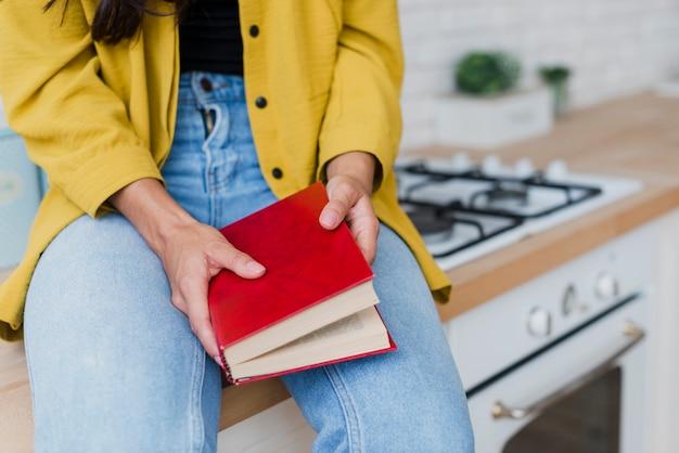 Mulher de close-up, segurando o livro com capa vermelha Foto gratuita