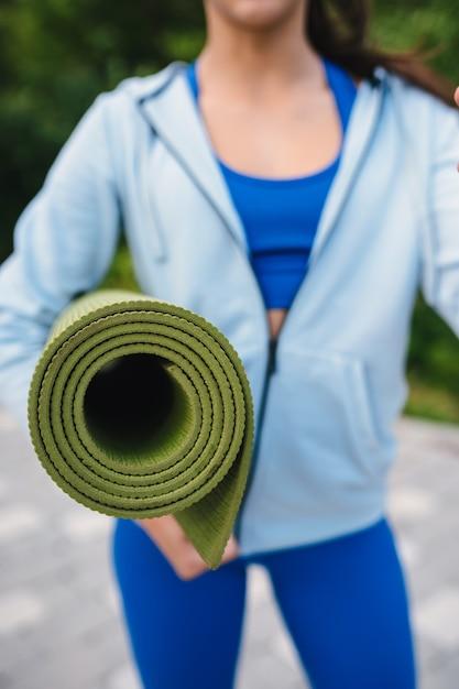 Mulher de close-up segurando roll fitness ou tapete de ioga depois de malhar no parque. Foto gratuita
