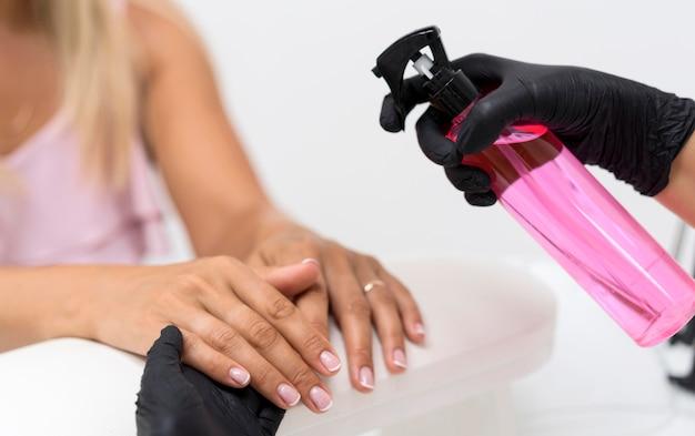 Mulher de close-up usando desinfetante para as mãos Foto gratuita