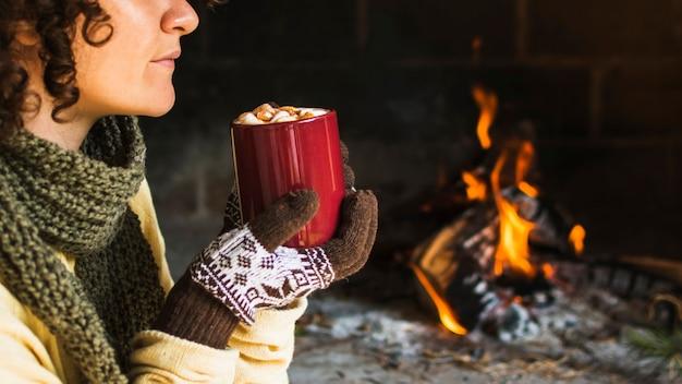 Mulher de colheita com bebida quente perto da lareira Foto gratuita