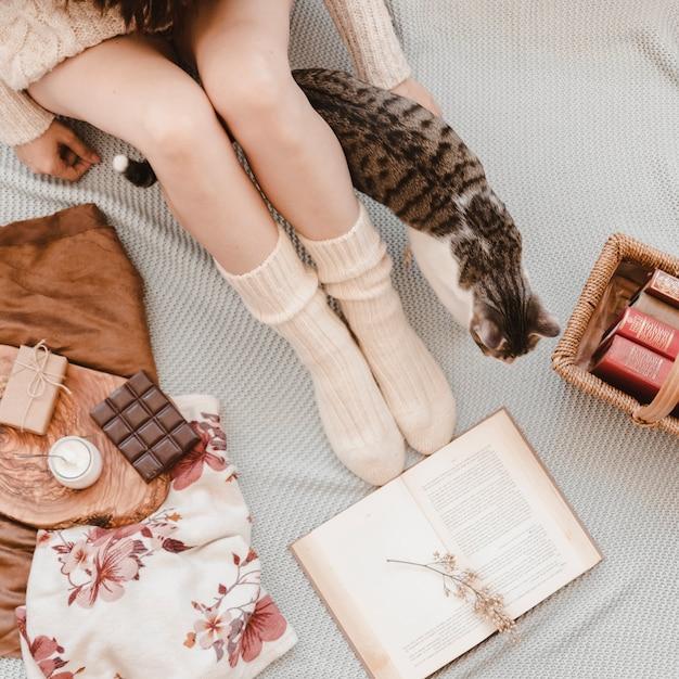 Mulher de colheita e gato no cobertor perto de livros e lanches Foto gratuita