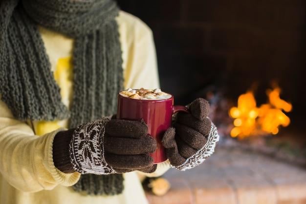 Mulher de colheita mostrando caneca de chocolate quente Foto gratuita