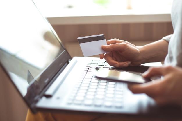 Mulher de compras on-line com um smartphone. as mãos da fêmea compram em linha guardarando um cartão de crédito com um portátil na tabela que senta-se em um café. Foto Premium