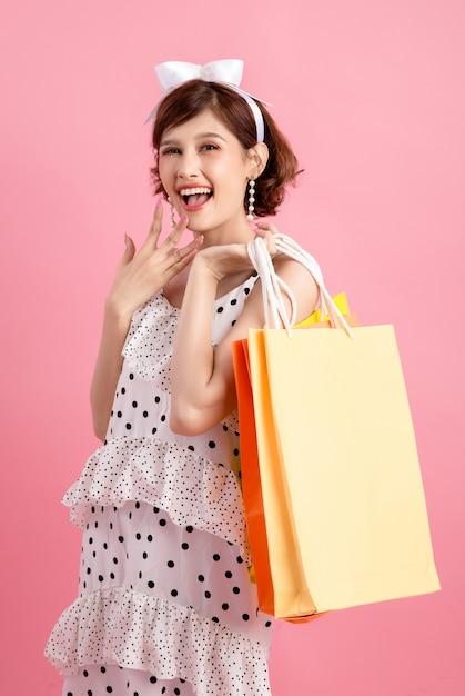 Mulher de compras segurando sacolas de compras em rosa Foto gratuita