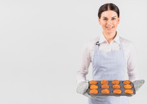 Mulher de confeiteiro sorrindo e segurando a lata de muffin Foto Premium