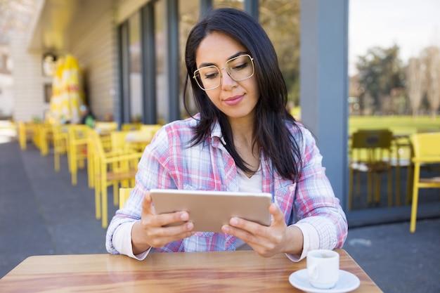 Mulher de conteúdo usando tablet e tomando café no café Foto gratuita