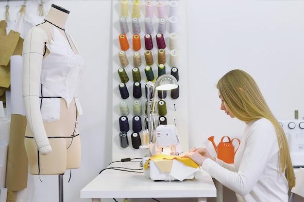 Mulher de costureira trabalhando com máquina de costura na oficina Foto Premium