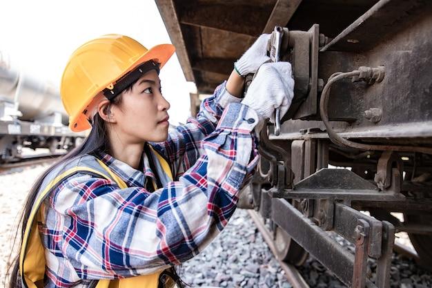 Mulher de engenheiros trabalhando no local da garagem do trem e usando uma chave inglesa para consertar o motor de tração do trem Foto Premium