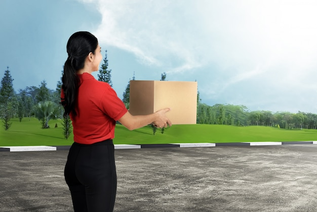 Mulher de entrega asiática feliz carregando o pacote Foto Premium