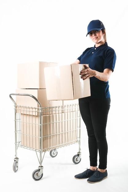 Mulher de entrega sorridente carregando caixa de encomendas na frente de fundo branco Foto gratuita