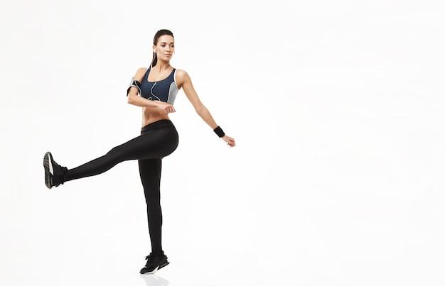 Mulher de esporte fitness em fones de ouvido, aquecendo o treinamento em branco. Foto gratuita
