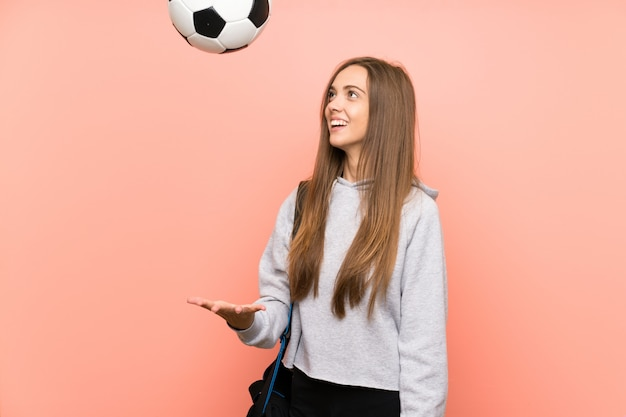 Mulher de esporte jovem feliz sobre fundo rosa isolado, segurando uma bola de futebol Foto Premium