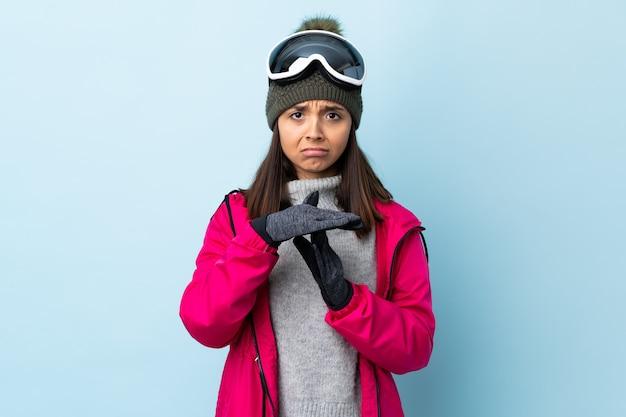 Mulher de esquiador de raça mista com óculos de snowboard sobre espaço azul isolado, fazendo o gesto de tempo Foto Premium