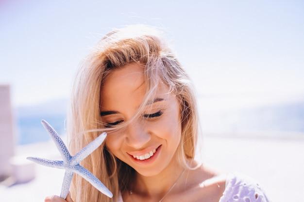 Mulher de férias segurando uma estrela do mar Foto gratuita