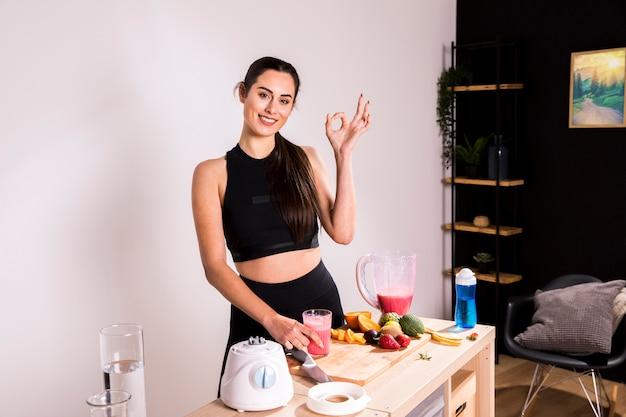 Mulher de fitness preparando um suco de desintoxicação Foto gratuita