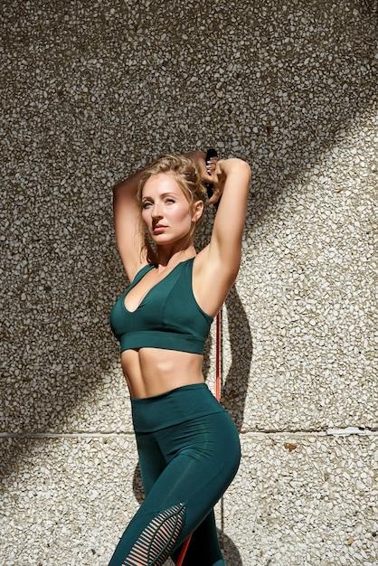 Mulher de fitness usando kettlebells fora durante o treinamento de força de aptidão contra copyspace Foto Premium