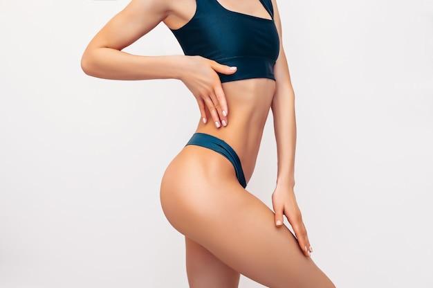 Mulher de forma irreconhecível em lingerie preta na parede branca isolada. mulher atraente magro muscular com barriga lisa. copie o espaço para texto. cuidados com o corpo, vida saudável e esportiva, conceito de remoção de pêlos Foto Premium