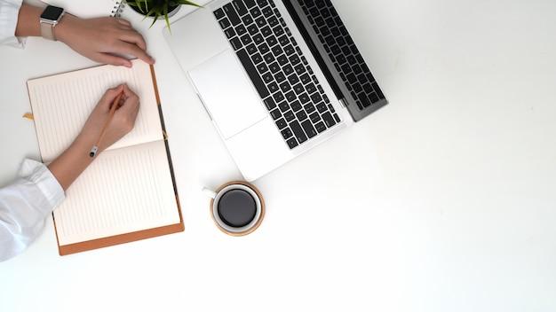 Mulher de funcionamento superior da vista que escreve notas no caderno no espaço de trabalho do escritório Foto Premium