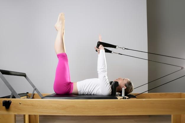 Mulher de ginástica pilates alongamento esporte na cama de reformador Foto Premium