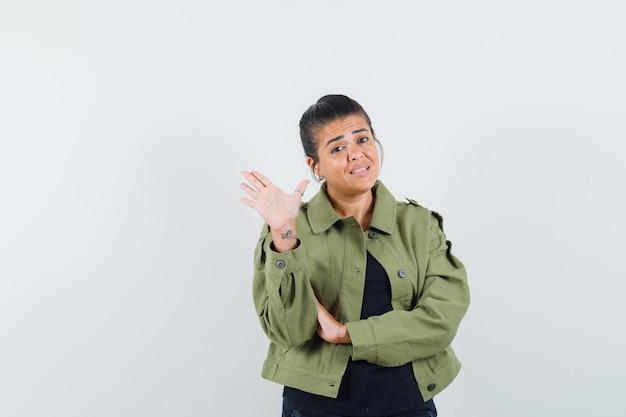 Mulher de jaqueta, camiseta mostrando cinco dedos e parecendo confiante Foto gratuita