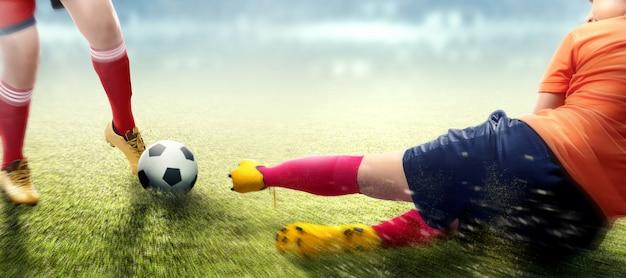 Mulher de jogador de futebol na camisola laranja deslizando enfrentar a bola do seu adversário Foto Premium