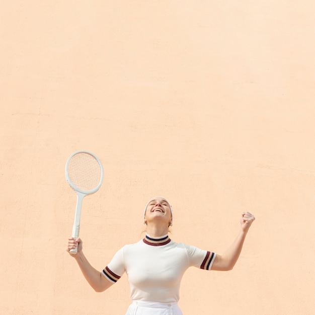 Mulher de jogador de tênis feliz por ganhar Foto gratuita