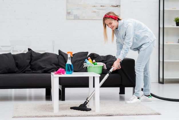 Mulher de limpeza com aspirador Foto Premium