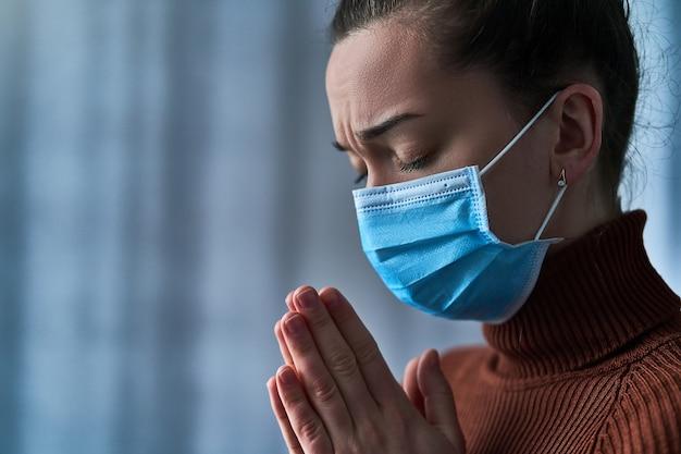 Mulher de máscara protetora com os olhos fechados e mãos a rezar, pede a deus cura e recuperação durante a doença Foto Premium