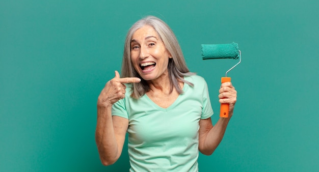 Mulher de meia-idade de cabelos grisalhos com um rolo de pintura decorando a parede Foto Premium
