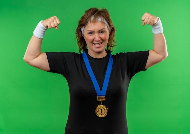 Mulher de meia-idade, esportiva, com camiseta preta, faixa para a cabeça e medalha de ouro em volta do pescoço, cerrando os punhos, feliz e animada em pé sobre a parede verde Foto gratuita