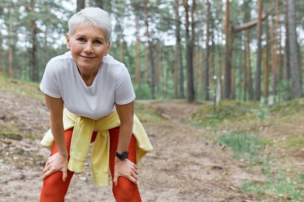 Mulher de meia-idade, esportiva, esguia, vestindo roupas esportivas, em pé no fundo de pinheiros Foto gratuita