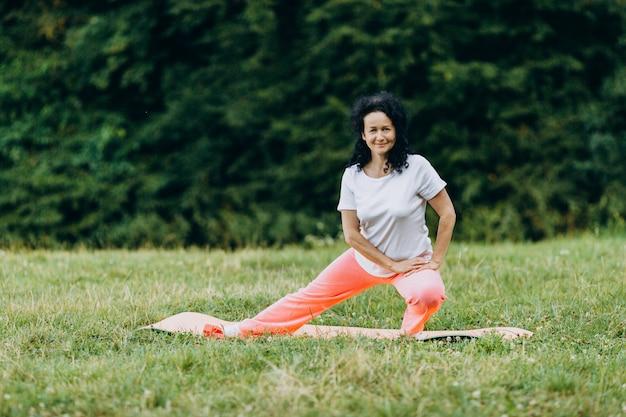 Mulher de meia idade fazendo exercício ao ar livre e esticando as pernas dela. esporte Foto Premium