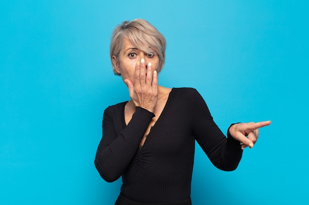Mulher de meia-idade feliz, chocada e surpresa, cobrindo a boca com a mão e apontando para o espaço lateral da cópia Foto Premium