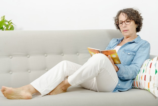 Mulher de meia idade lê, sentado no sofá Foto Premium
