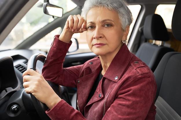 Mulher de meia-idade moderna bem-sucedida em roupas elegantes, com rosto facial perturbado dentro do carro Foto gratuita