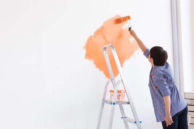 Mulher de meia-idade muito sorridente, pintando a parede interior da casa com rolo de pintura. Foto Premium