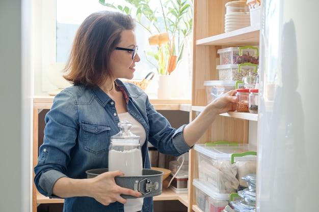 Mulher de meia idade, pegar comida do armário de armazenamento na cozinha Foto Premium