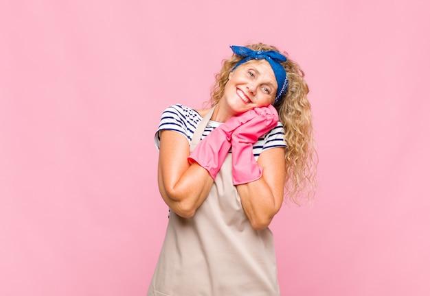 Mulher de meia idade se sentindo apaixonada e parecendo fofa, adorável e feliz, sorrindo romanticamente com as mãos ao lado do rosto conceito de governanta Foto Premium