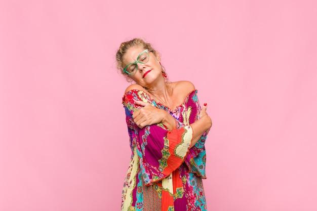 Mulher de meia-idade se sentindo apaixonada, sorrindo, acariciando e abraçando a si mesma, permanecendo solteira, sendo egoísta e egocêntrica Foto Premium